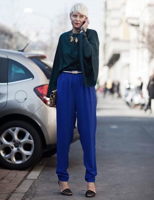 Pantone elije el classic blue como el color del 2020; chica de cabello pixie, color blanco, con blusa de mangas holgadas verde y pantalones azul clásico, bolsa de mano de animal print, chica hablando por celular