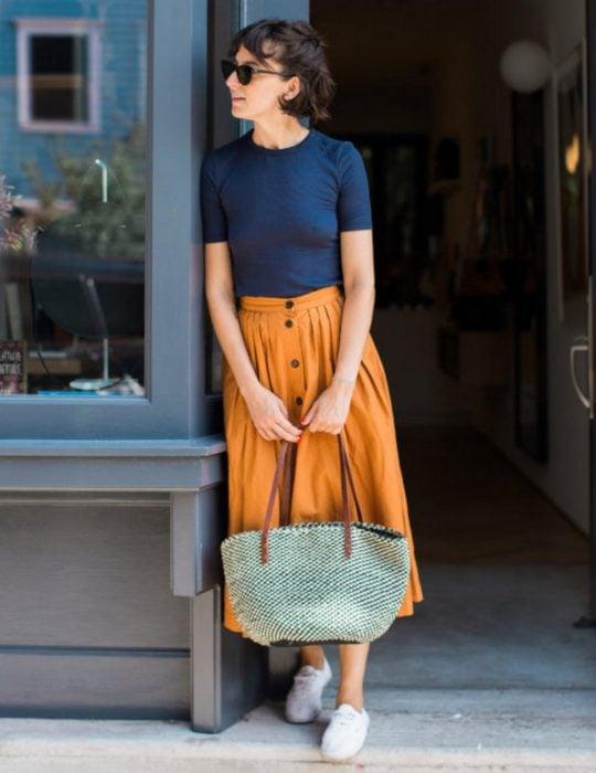 Pantone elije el classic blue como el color del 2020; mujer de cabello corto con blusa azul clásico, falda midi anaranjada y bolsa tejida