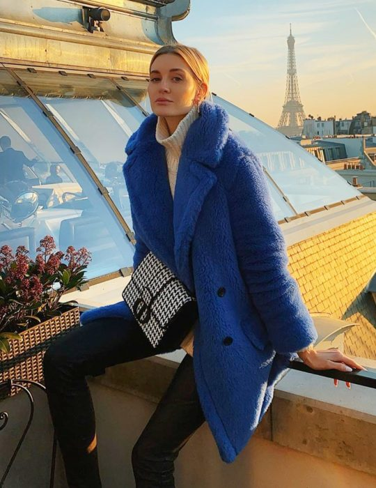 Pantone elije el classic blue como el color del 2020; mujer rubia sentada en balcón, abrigo de pana azul clásico