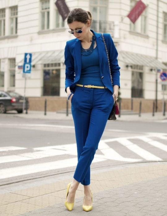 Pantone elije el classic blue como el color del 2020; mujer en la calle con traje azul clásico, pantalón y saco de vestir con zapatillas amarillas