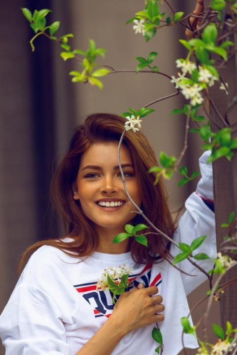 Chica conriendo detrás de un arbusto con plantas