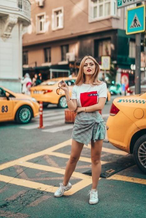 Chica caminando entre una avenida transitada de nueva york