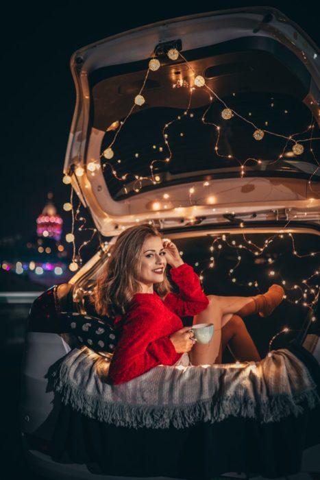 Chica dentro de un automóvil lleno de luces en la cajuela