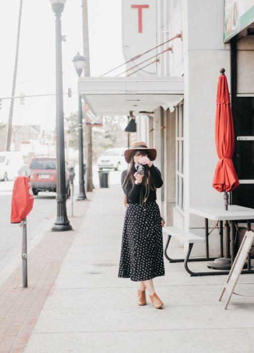 Chica sosteniendo una cámara fotográfica
