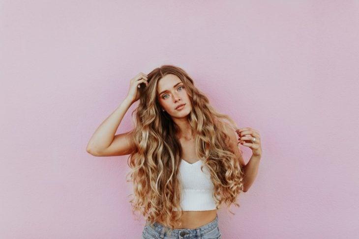 Ragazza con i capelli lunghi, biondi e ricci carichi su una parete rosa pastello