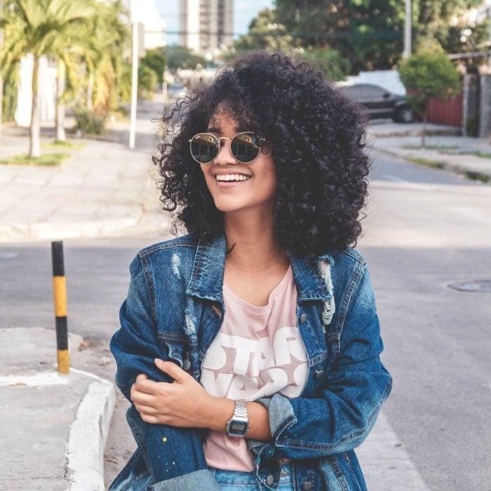 Chica de cabello rizado co chaqueta de mezclilla caminando por la calle y sonriendo