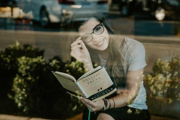 Chica leyendo un libro dentro de una cafetería y sonriendo