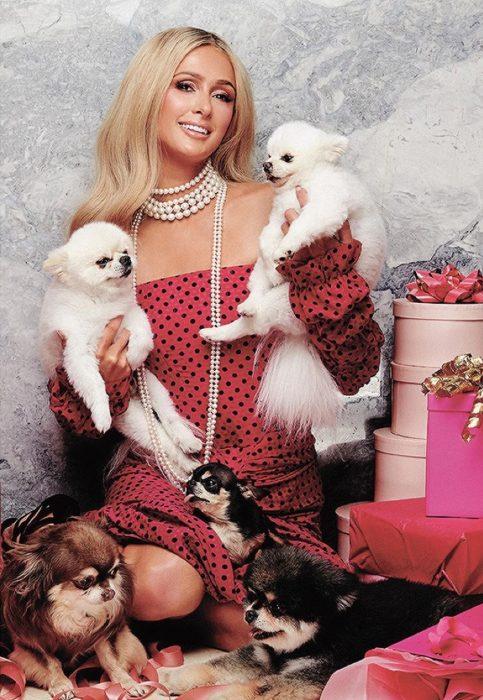 Paris Hilton posando para una fotografía con sus perritos