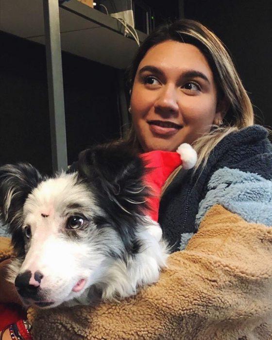 Chica abrazando un perro pastor entre sus brazos