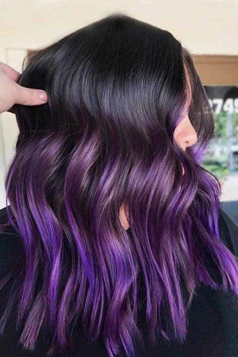 Chica mostrando su cabello de color dark violeta estilo belayage