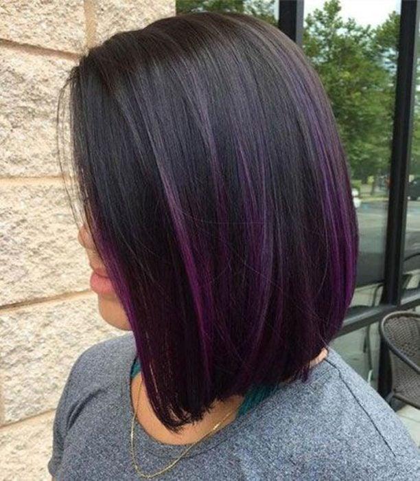 Chica mostrando su cabello de color dark violeta con un corte bob