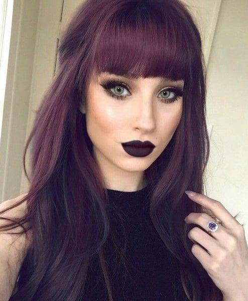 Chica mostrando su cabello de color dark violeta con flequillo y labios del mismo color