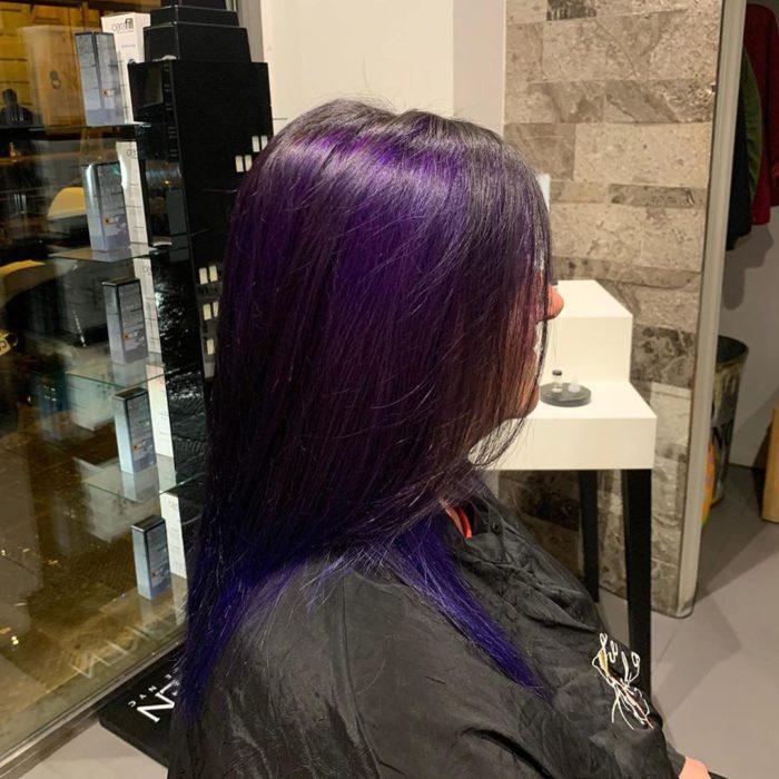 Chica mostrando su cabello de color dark violeta después de que se lo tiñeron