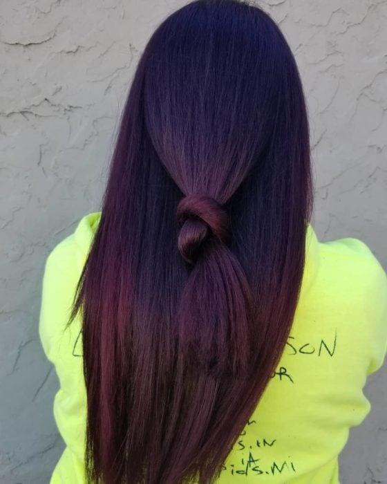 Chica mostrando su cabello de color dark violeta sujetado en una coleta