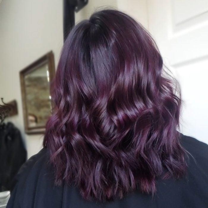 Chica mostrando su cabello de color dark violeta con destellos que brillan en la luz