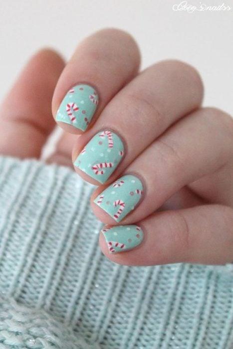 Uñas cortas en color menta con sticker en diseños de bastón de caramelo