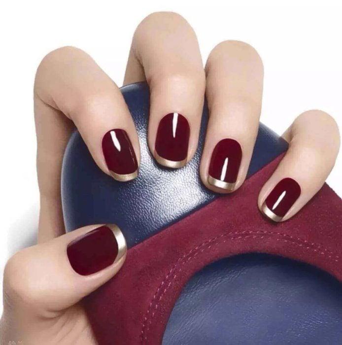 Uñas de manicure francesa en color vino con dorado