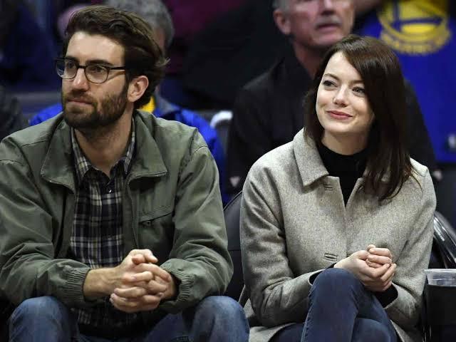 Emma Stone y Dave McCary sentados, mirando un partido de basquet