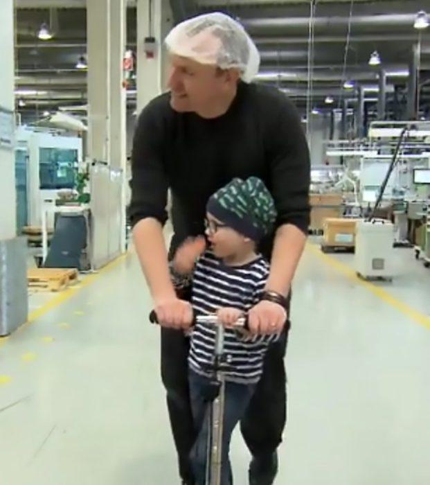 Padre e hijo jugando en un patín dentro de una fabrica