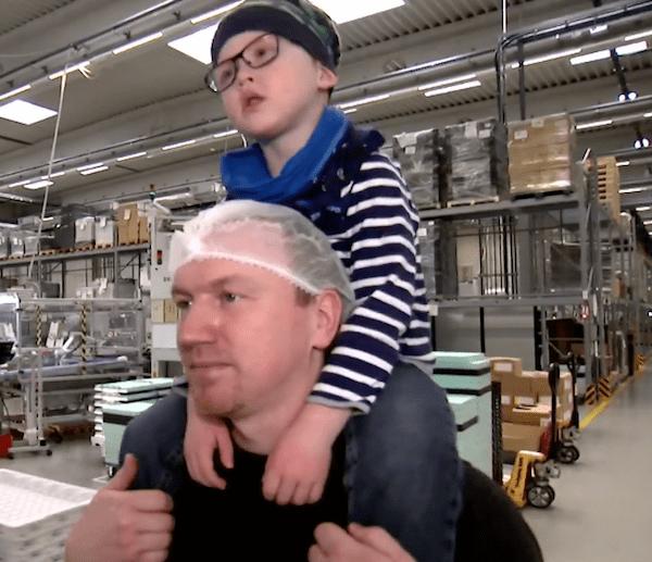 Padre cargando a su hijo en hombros dentro de una fábrica