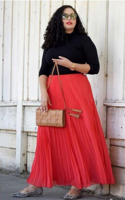 chica con falda plisada coral y blusa negra de manga larga