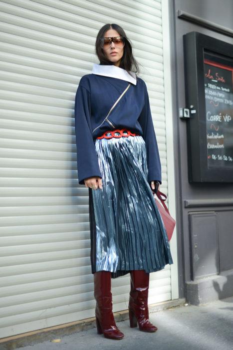 chica con suéter azul oscuro y dalda larga plisada azul con toques blancos