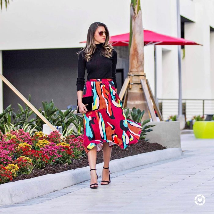chica con blusa negra y falda plisada en tonos rojos