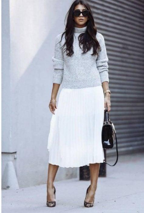 Chica con suéter gris y falda plisada blanca larga