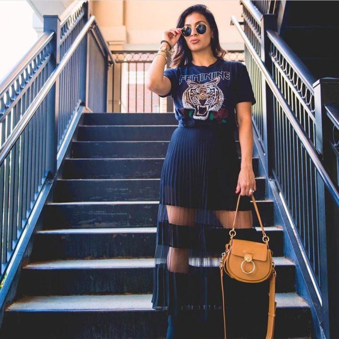 chica camiseta de banda y falda larga plisada transparente