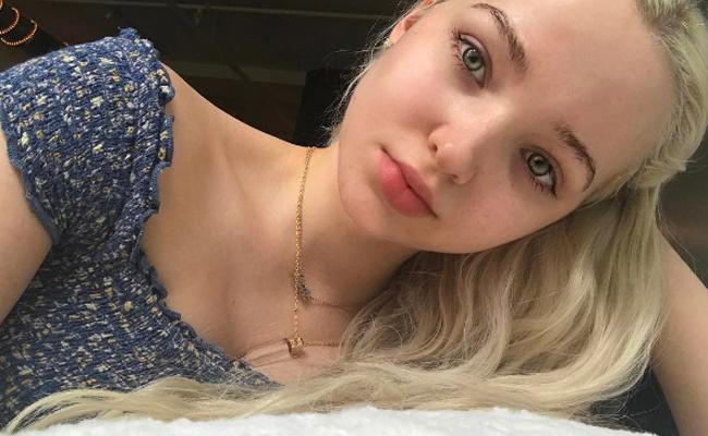 Dove Cameron sin maquillaje, recostada, tomando una selfie