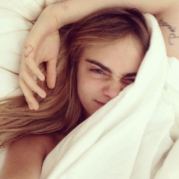 Cara Delevingne sin maquillaje, recostada en su cama, cubriendo su rostro con una sabana blanca