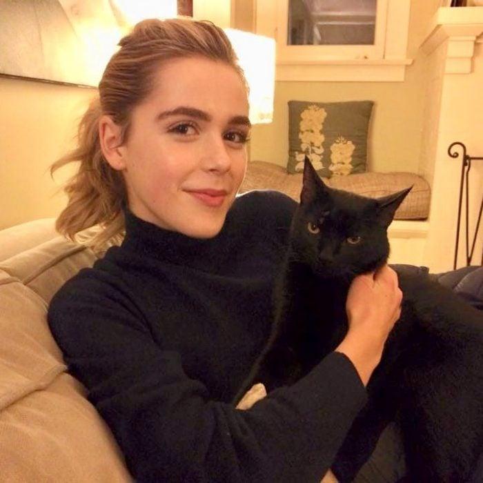 Kiernan Shipka sin maquillaje, sentada en un sofá, acariciando a su gato