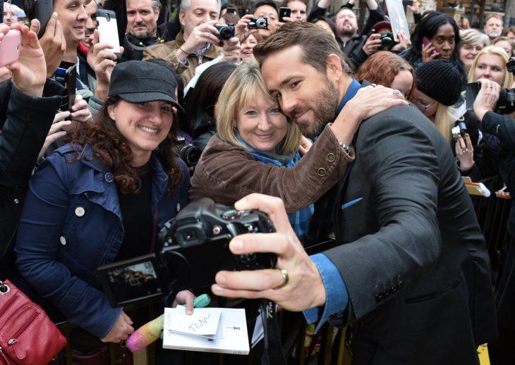 Ryan Reynolds sosteniendo una cámara para tomar una selfie con sus fans