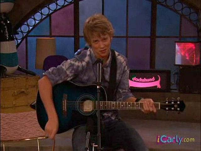 Austin Butler sentado en un banquito tocando guitarra en iCarly