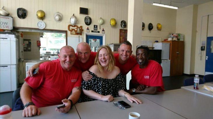 Adele junto a un grupo de bomberos sonriendo