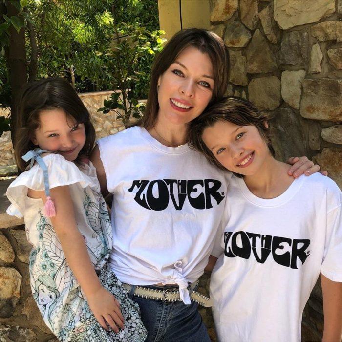 Milla Jovovich abrazando a sus hijas para una foto
