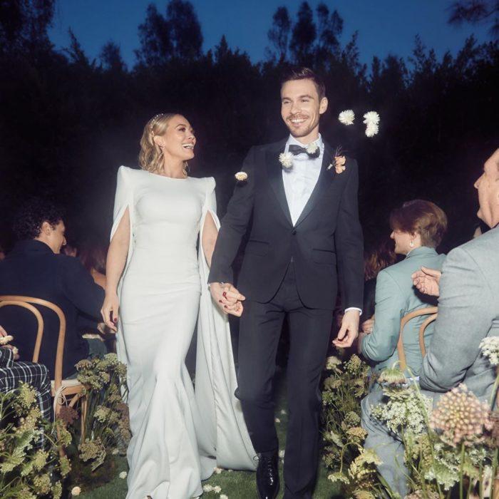 Hilary Duff y su esposo Matthew Koma caminando hacia el altar tomados de la mano
