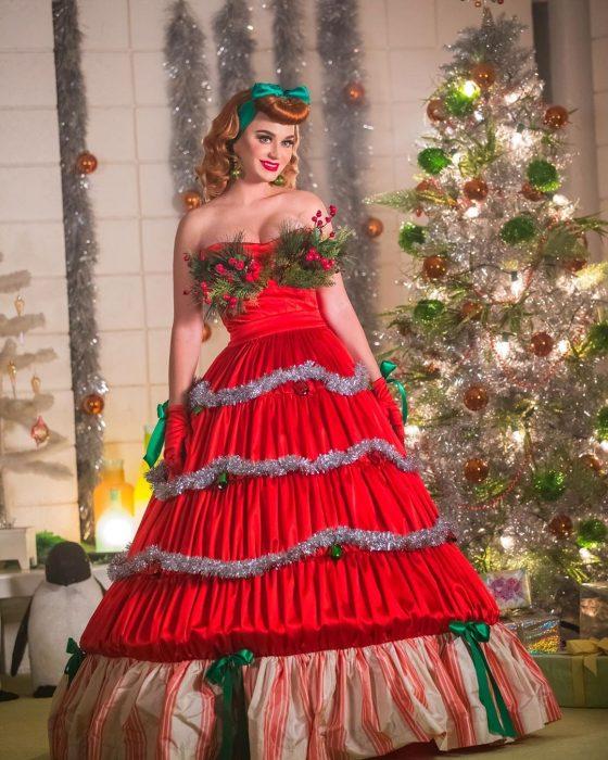 Katy Perry usando un vestido navideño de color rojo mientra posa para una sesión de fotos junto a un árbol