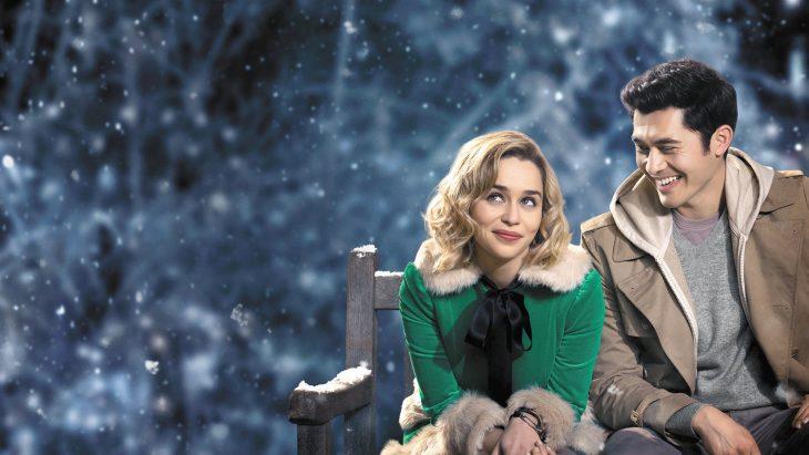 Emilia Clarke y Henry Golding sentados en una banca mientras actuan en la película Last Christmas