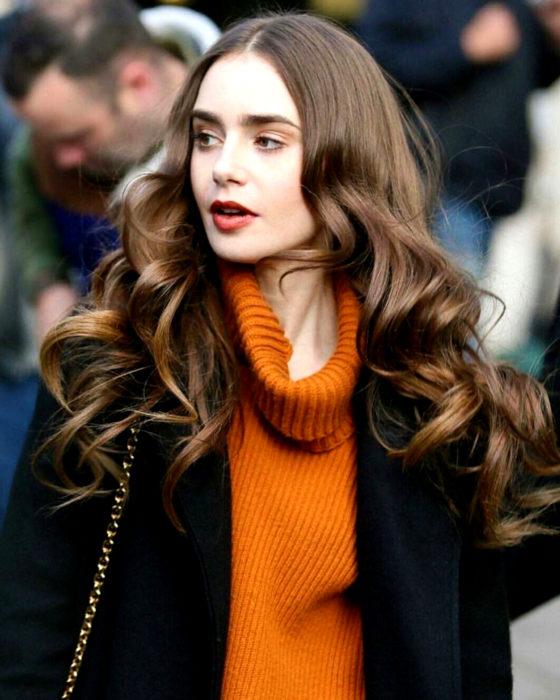 Peinados de Lily Collins para Año Nuevo; mujer de cabello castaño, largo, ondulado, con suéter de cuello de tortuga anaranjado