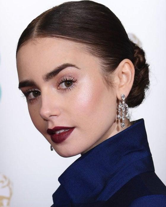Peinados de Lily Collins para Año Nuevo; mujer de cabello lacio, castaño, recogido en un chongo bajo, maquillaje natural y labios color vino