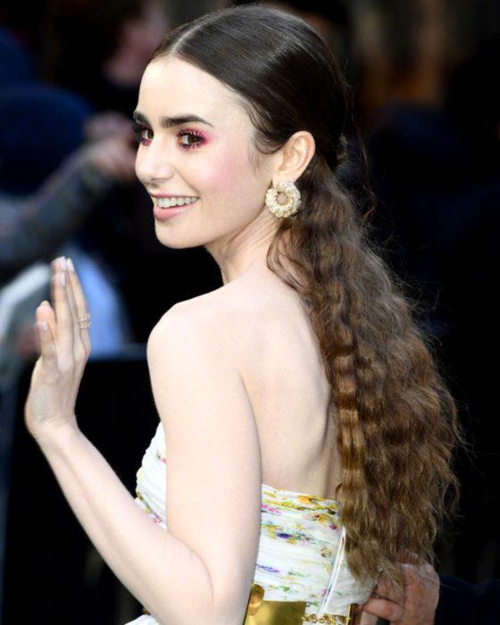 Peinados de Lily Collins para Año Nuevo; mujer de cabello largo, castaño, ondulado con wafflera, agarrado en media cola, con maquillaje natural y aretes grandes