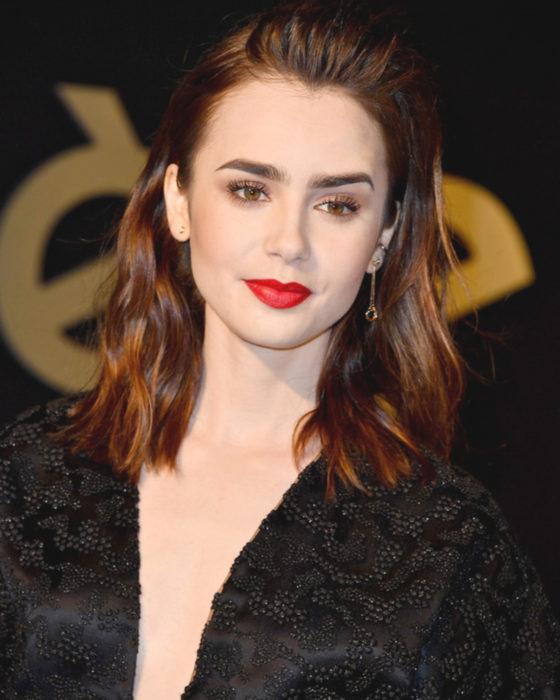 Peinados de Lily Collins para Año Nuevo; mujer de cabello castaño rojizo con efecto mojado, maquillaje natural