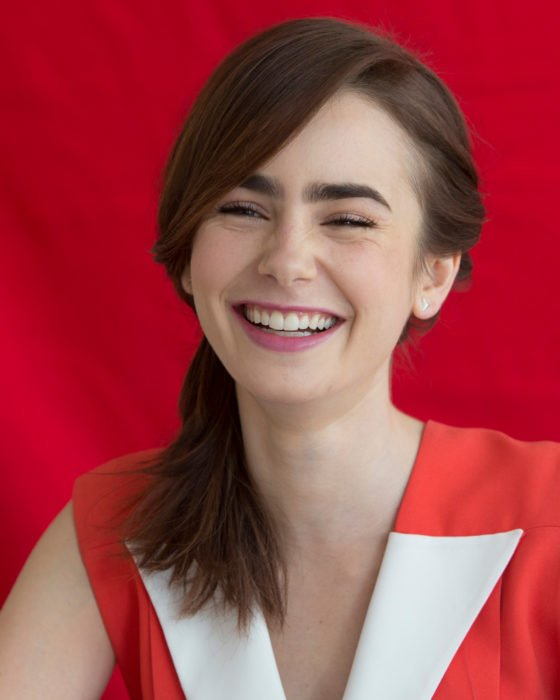 Peinados de Lily Collins para Año Nuevo; mujer de cabello lacio, mediado, castaño recogido en una coleta de lado, chica riendo
