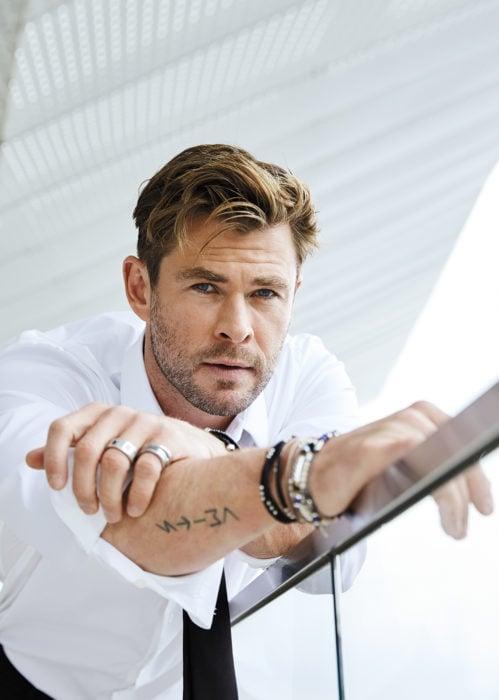 Chris Hemsworth recargado en una escalera posando