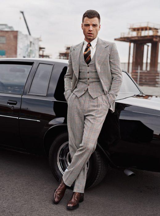 Sebastian Stan recargado en un automóvil viejo