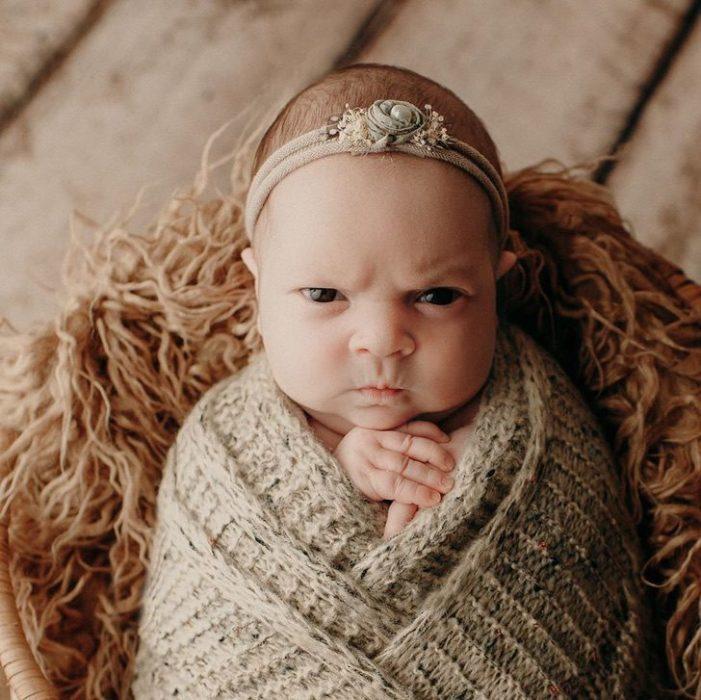 bebé recostada en una canastilla durante una sesión de fotos de nacimiento