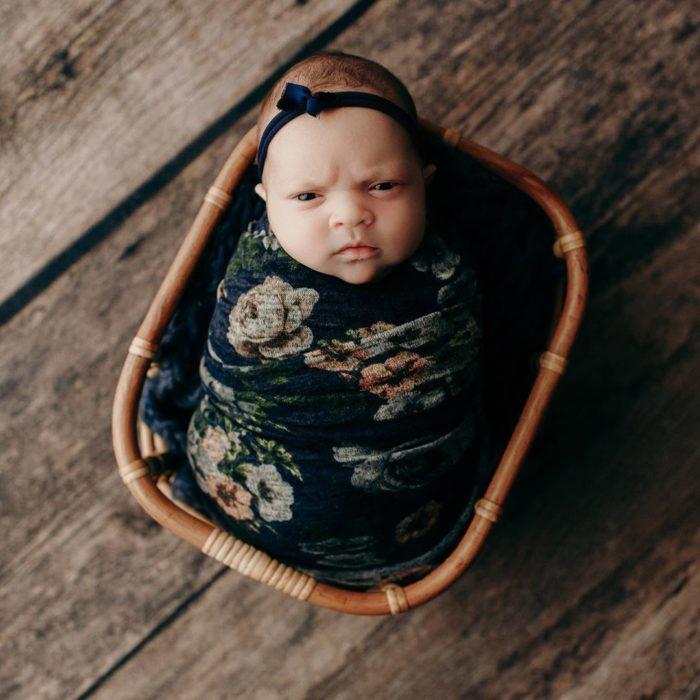 Bebé recostada en una canastilla durante una sesión de fotos con el rostro de molestia