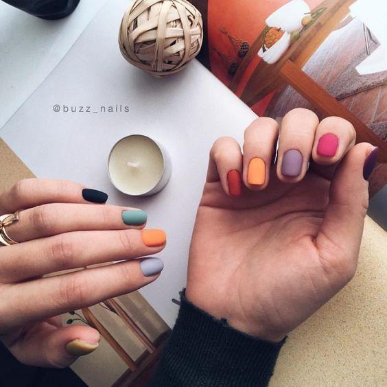 Chica mostrando su manicura de colores