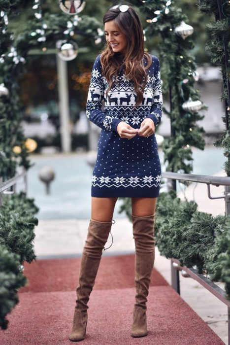 Chica usando un vestido con estampado de suéter feo en color azul con unas botas largas de color café